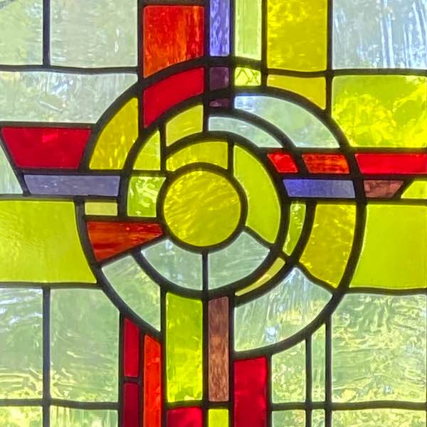 Stained glass window from Church of St. Ciaran showing a red cross with yellow and blue glass